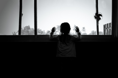 Asian child girls are standing in the dark, looking out the window,sad mood, black and white tones.