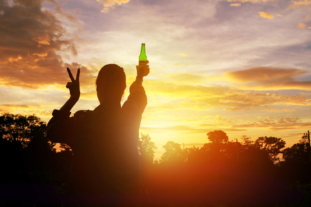 manos levantadas al cielo: Silhouette woman raised hands holding a green beer bottle on the sunset sky,