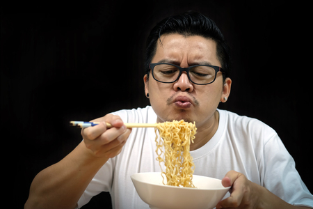 Asian man eating Instant noodles on black background