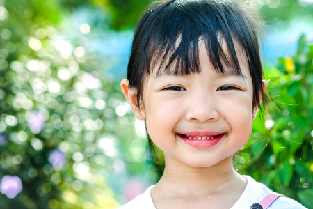 brightly: asian child girl smiling brightly with happiness.