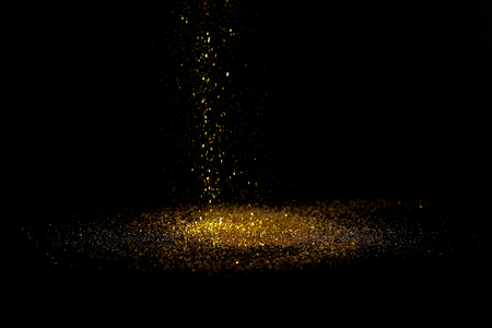 Sprinkle gold dust on a black background with copy space.