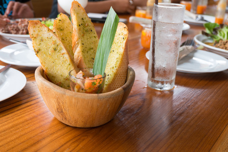 Garlic bread in a wooden bowl on the table Stock Photo