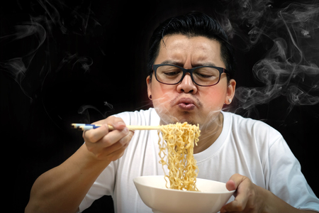 Asian man eating Instant noodles very hot and spicy on black background