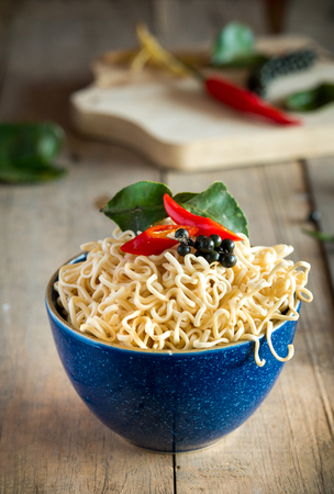 Instant noodles in a bowl with chili pepper and lime leaves on old wooden table Stock fotó - 72809379