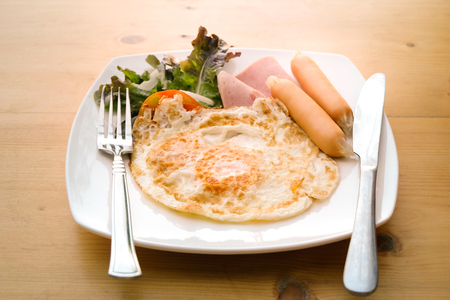 Breakfast with fried eggs, bacon, sausage and fresh salad on white dish with fork and knife.