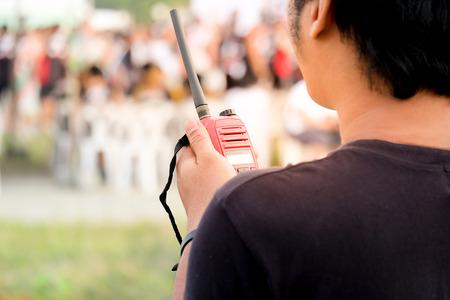 Mann mit einem Walkie Talkie oder einem tragbaren Radio-Transceiver für die Kommunikation Standard-Bild - 72809214