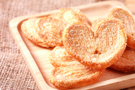 Paddle a butterfly, heart shaped patty crispy with sugar in a wooden dish for lovers on Valentines Day