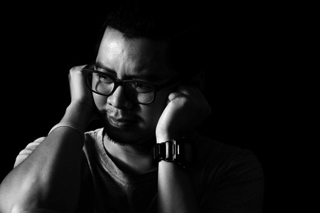 Asian man in the darkness covers his ears in the mood to hear about any depression Stock Photo