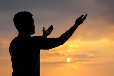 silhouette of a man with hand up on sunset background, The concept the blessings from heaven