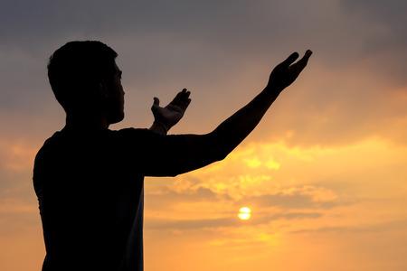 silueta de un hombre con la mano arriba en el fondo del atardecer, el concepto de las bendiciones del cielo Foto de archivo