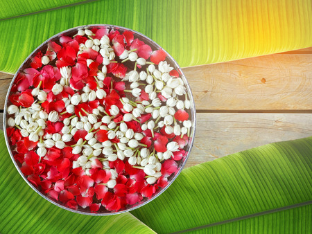 Jasmine and roses in silver bowl on leaves of  banana ,Songkran festival in Thailand