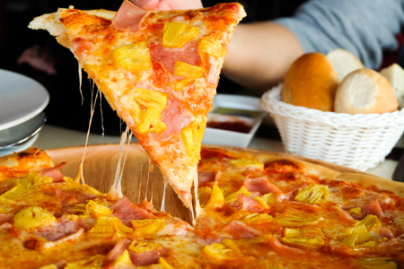 Close up Womans hand picked Hawaiian pizza from a wooden tray on the table.