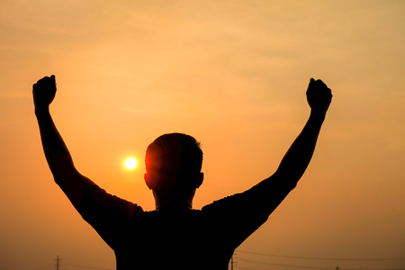 Man silhouette holds up his arms fist as the winner at sunset.