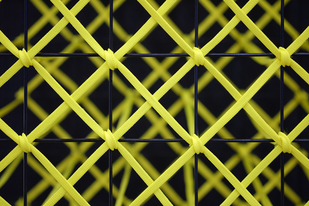 Yellow rope tied to a black steel grill, Abstract texture background Stock Photo