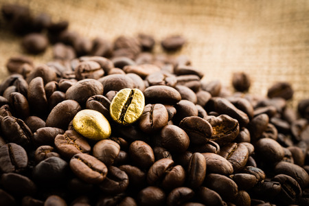 Gold coffee beans on a pile of coffee beans. The concept of luxury is extraordinary.