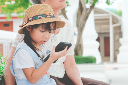 Asian child girls are addictive playing mobile phones, Game Addiction Stock Photo