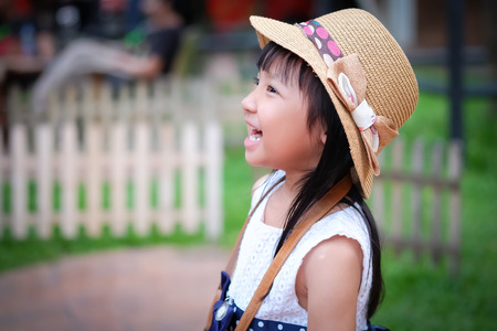 Asian little girl watching his activity ahead and laughing emotionally.