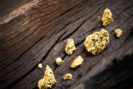 Pure gold ore on old wooden floor Imagens