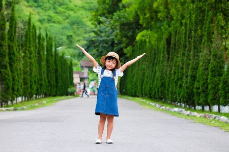 Asian child girl smiling with her arms raised on both sides of the road. With green trees