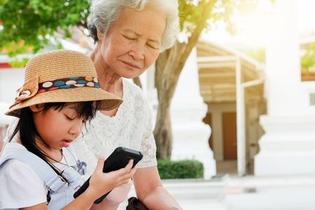 Asian child girl is addictive, play mobile phone addicted to the game, have an elderly grandmother sit with caring concern, family generation.