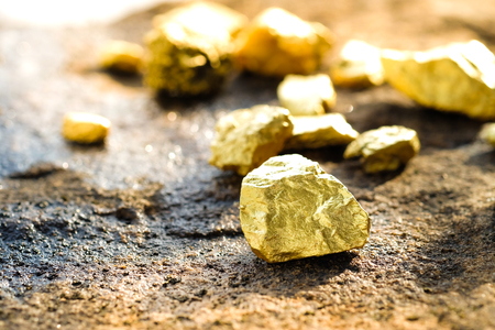 The pure gold ore found in the mine on a stone floor Foto de archivo
