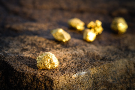 The pure gold ore found in the mine on a stone floor Stock Photo