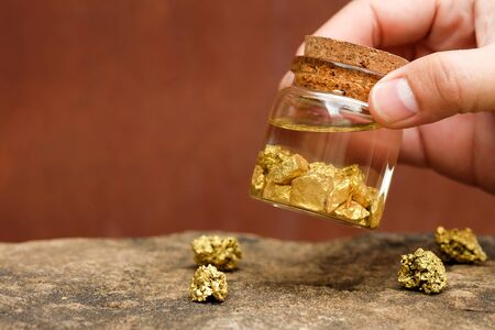 Human hands are holding bottles that contain pure gold minerals found in mines on black background Stock Photo