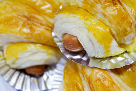 Close up baked bread put sausage on a foil