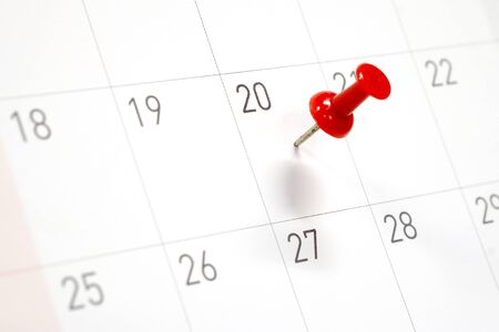 Embroidered red pins on a calendar on the 20th with selective focus