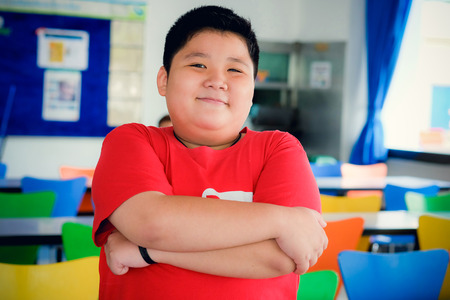 Asian obese boy standing crossed arms and cute smile Stockfoto
