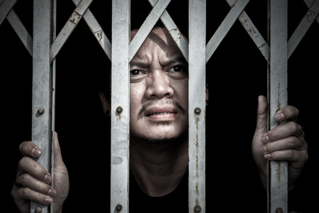 Asian men are trapped in steel cages and look out to sad faces.