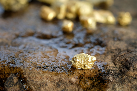 The pure gold ore found in the mine on a stone floor Standard-Bild