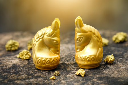 Vintage chess horse in gold and gold on old stone floor. Conception of prosperity Stock Photo