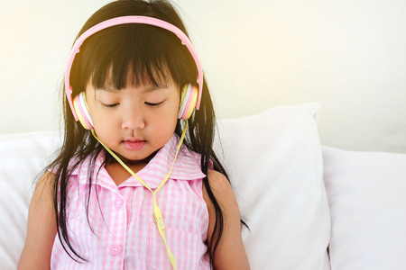 Asian girl wearing headphones Watching happy video clips on bed, lifestyle Childrens digital age Reklamní fotografie