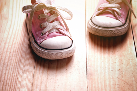 Pink girl sneakers on a wooden floor with copy space Reklamní fotografie