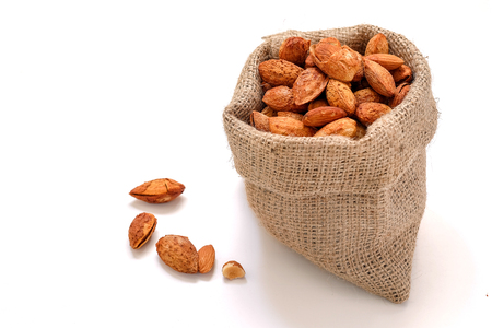 Almond nuts in the shell In sackcloth on white background