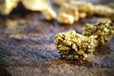 The pure gold ore found in the mine on a stone floor Reklamní fotografie