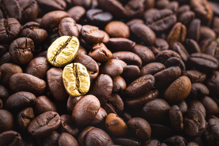 Gold coffee beans on a pile of coffee beans. The concept of luxury is extraordinary. Standard-Bild - 103383729