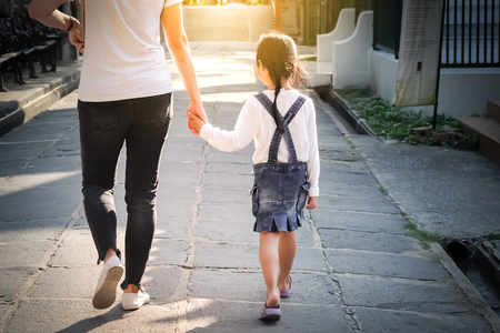 The girl is walking hand in hand with her mother on the street.