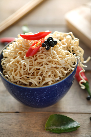 Instant noodles in a bowl with chili pepper and lime leaves on old wooden table