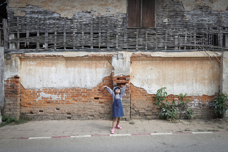 Asian child girl Post with the front of the old brick wall happily