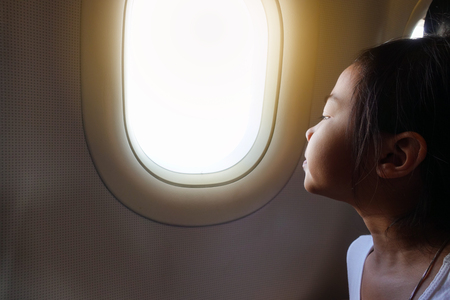 Asian child girl is sitting and looking outside the window of the plane interested. Reklamní fotografie