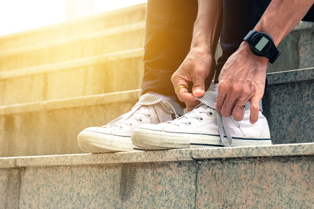 Men are sitting and tying white sneakers.