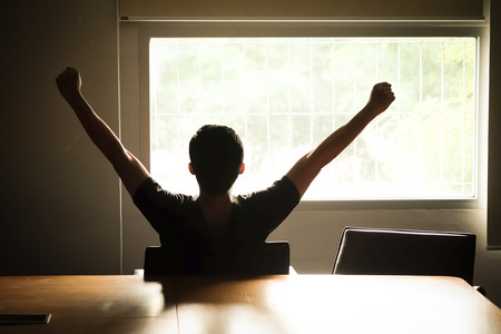 Asian men are holding their arms and fists to loosen their gaze out of the morning window, ready for the first days work.
