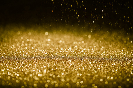 Sprinkle glitter gold dust in the dark textured abstract background elegant for Merry christmas and Happy new year