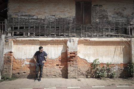 Asian man standing with the front of the old brick wall