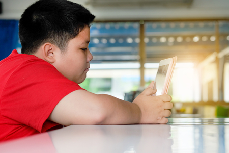 Asian child Boy are addictive playing tablet and mobile phones, Game Addiction