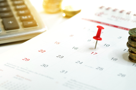 Embroidered red pins on a calendar on the 17th with selective focus, Tax day Concept Reklamní fotografie