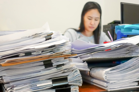 Many documents on the employee's desk with selective focus
