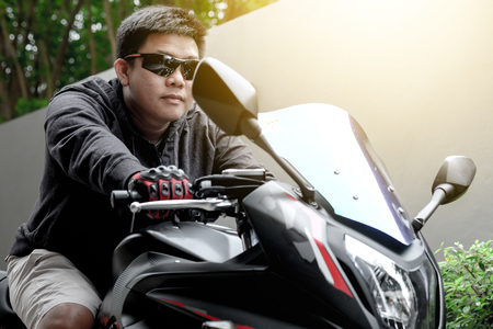 Asian guy wearing sunglasses riding a motorcycle